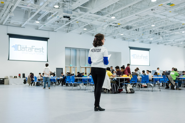 Mentor standing in front of tables with students