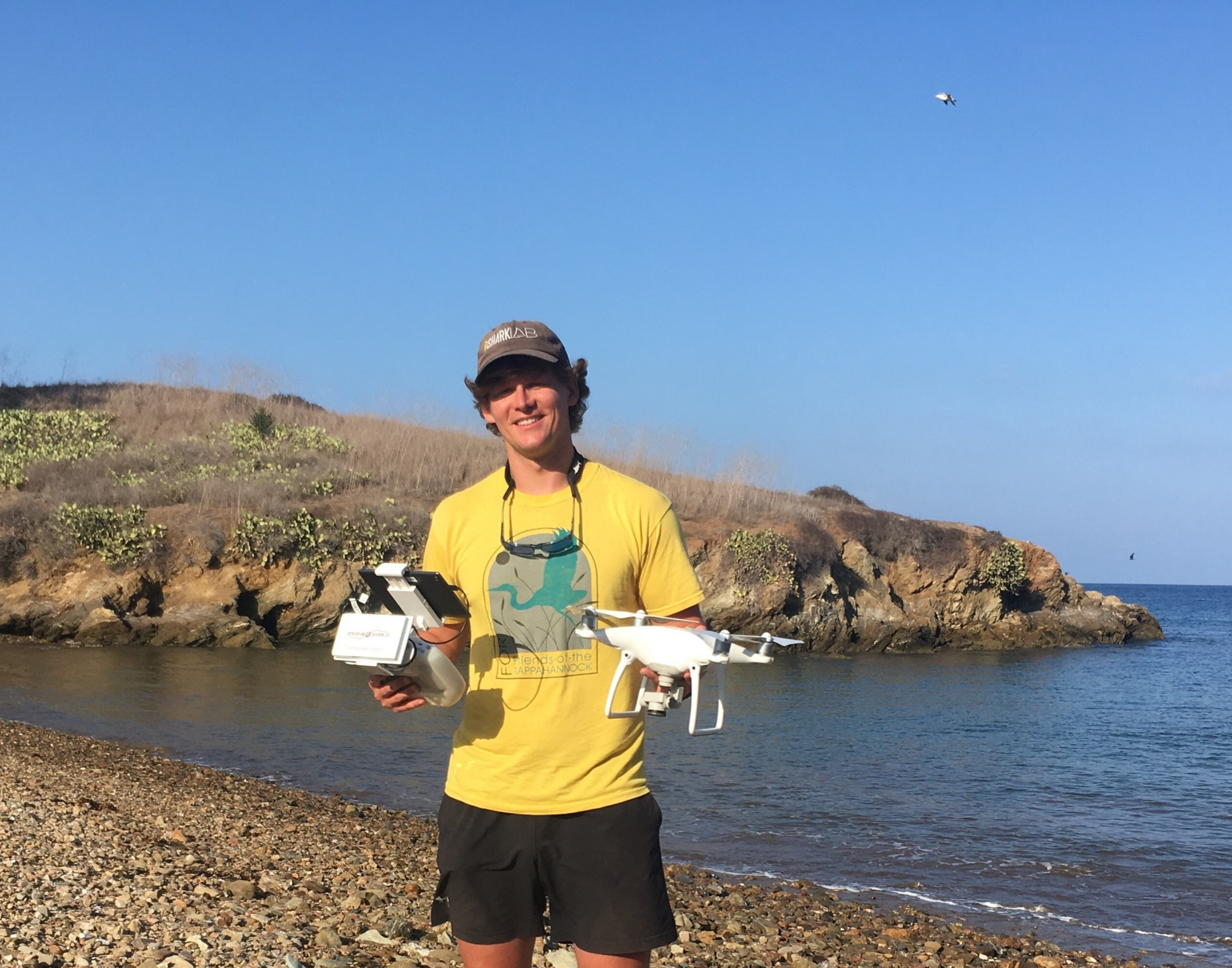 Researcher Jack May holding a drone and temperature loggers used to collect data on sharks