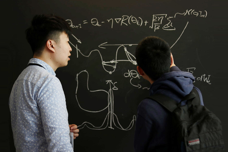 Two students discuss statistical graph on chalkboard
