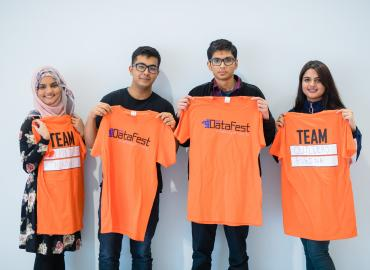 Team of undergrad students holding up DatFest shirts
