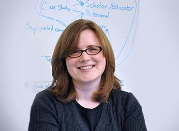 Alison Gibbs standing in front of a whiteboard.