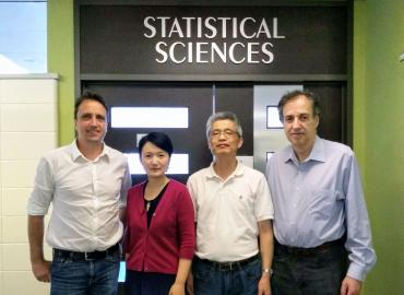 Department faculty members posing under Statistical Sciences sign